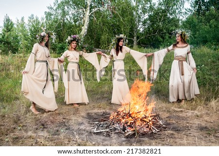 Attractive Women in traditional clothes with Wreath of Flowers dancing around bonfire. Ivan Kupala Holiday Celebration. Russia - stock photo