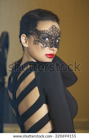 Attractive women with black lace mask, standing on stairs and looking seductively towards the camera. Shallow depth of field. Selective focus. - stock photo