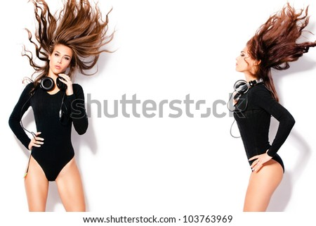 attractive women with headphones in dancing motion, hair fly, wearing tight black body, studio white