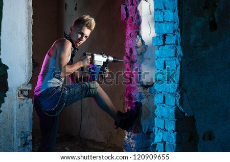 Attractive worker holding a drill in his hands