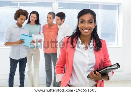 Attractive worker with planner smiles at camera with colleagues in background in the office - stock photo