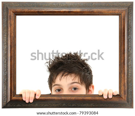 Attractive 8 year old boy peeking out of ornate stained wooden frame over white isolation. - stock photo