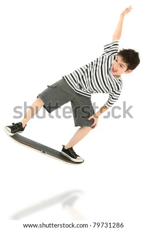 Attractive 8 year old boy playing on video game skateboard controller jumping over white background. - stock photo