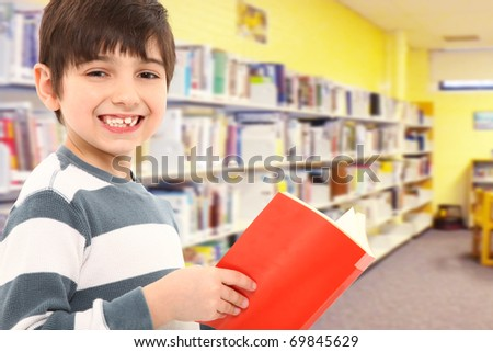 Attractive 7 year old boy with book in school library smiling at camera. - stock photo