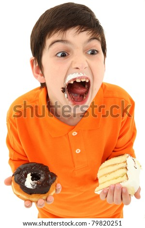 Attractive 8 year old boy with insane expression and hands full of sweets over white.