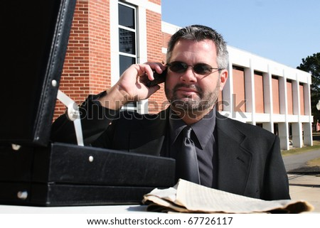 Attractive 40 year old business man in suit and sunglasses on phone outside.