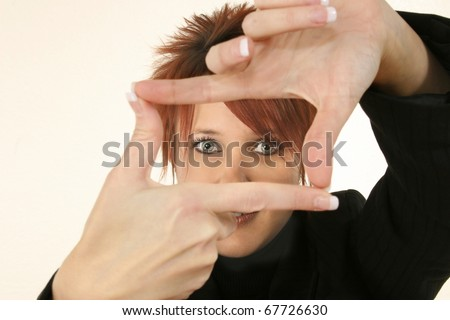 Attractive 30 year old business woman with manicured nails making video camera gesture with hands.