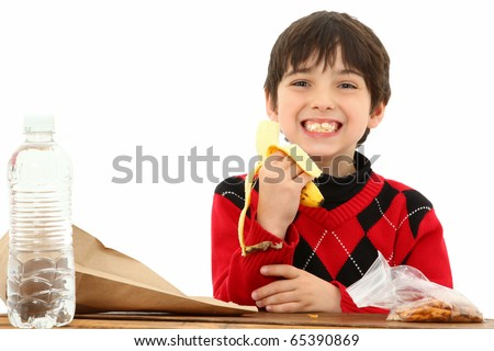 Attractive 7 year old french american boy in school desk over white eating a sack lunch or snack. - stock photo
