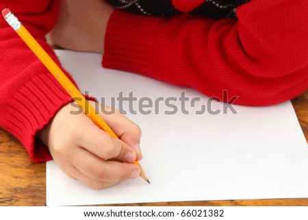 Attractive 7 year old french american boy in school desk over white writing on paper. - stock photo