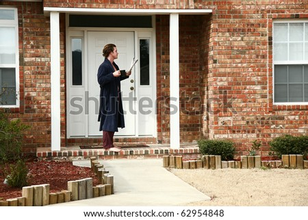 Attractive 35 year old man in robe drinking coffee and reading newspaper outside home front door. - stock photo
