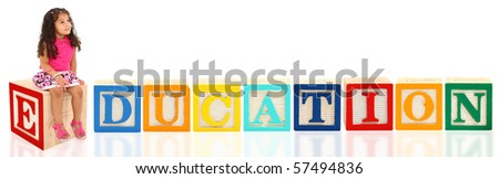 Attractive 3 year old mixed race american girl sitting on wooden block day-dreaming over white background. Blocks spell Education. - stock photo