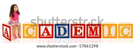 Attractive 3 year old mixed race american girl sitting on wooden block spelling Academic. - stock photo