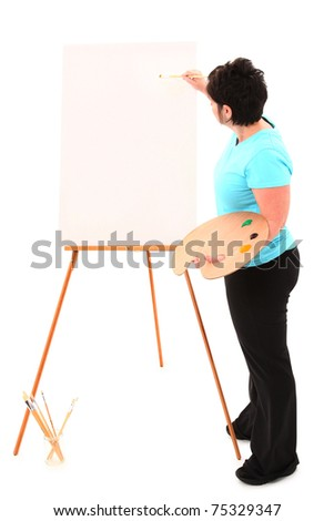Attractive 40 year old overweight french american woman at blank canvas easel painting over white with clipping path.