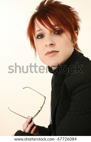 Attractive 30 year old woman with serious expression holding glasses in suit. - stock photo