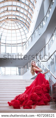 Attractive yong woman in magnificent puffy red dress on the staircase - stock photo