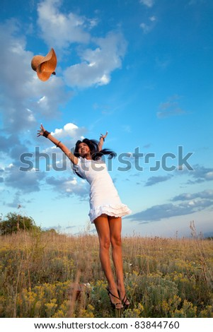 Attractive yong woman is jumping and throwing her hat. Rural evening background. - stock photo