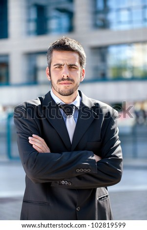 Attractive young adult business man looking at camera.
