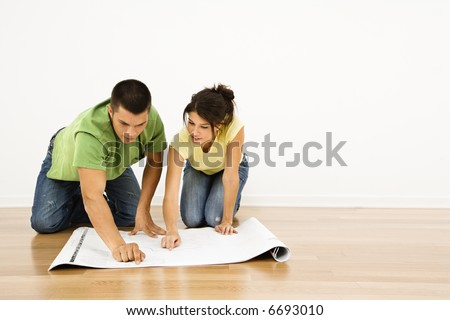 Attractive young adult couple looking at house plans. - stock photo