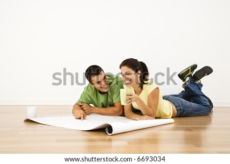 Attractive young adult couple lying on home floor with coffee cups smiling and looking at blueprints. - stock photo