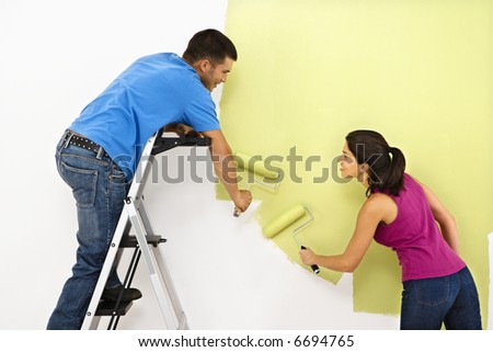 Attractive young adult couple painting interior wall of house. - stock photo