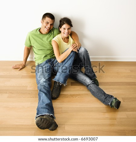 Attractive young adult couple sitting close on hardwood floor in home smiling. - stock photo