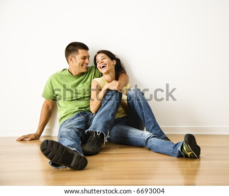 Attractive young adult couple sitting close on hardwood floor in home smiling and laughing. - stock photo