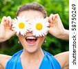 attractive young adult covering her eyes with white chamomile and laugh out loudly - stock photo
