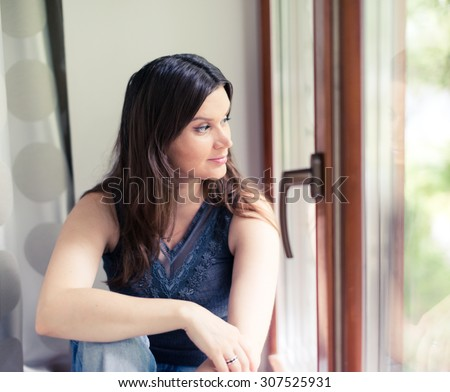 attractive young adult looking at the window