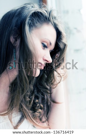attractive young adult looking at the window with serious look - stock photo