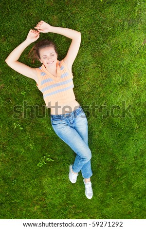 attractive young adult lying down on green grass and relax