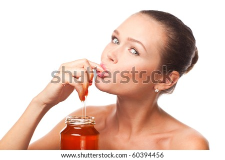 attractive young adult with honey holding finger in the mouth isolated on white background - stock photo