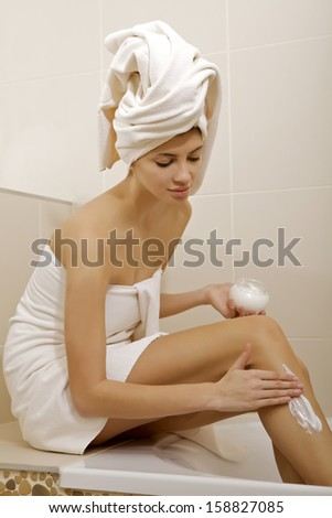 Attractive young adult woman applying moisturizer cream on the legs in bathroom - stock photo