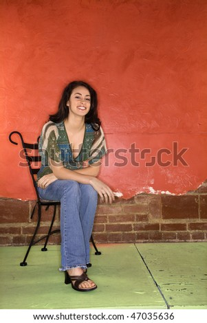 Attractive young adult woman sitting on a chair in front of a colorful wall. Vertical shot. - stock photo
