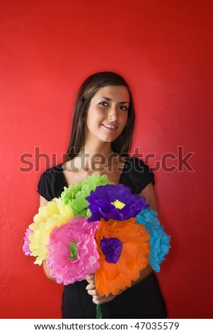 Attractive young adult woman standing against a red wall holding a bouquet of colorful paper flowers. Vertical shot. Isolated on red.