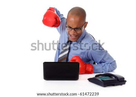 Attractive young African American businessman in office, wearing boxing gloves. Ready to hit the laptop . Studio shot. White background. - stock photo