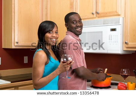Attractive young African American couple cooking dinner together and drinking red wine.  Horizontally framed shot with the man and woman looking towards the camera. - stock photo