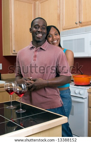 Attractive young african american couple standing in their kitchen. She is standing behind him and hugging him. Vertically framed shot.