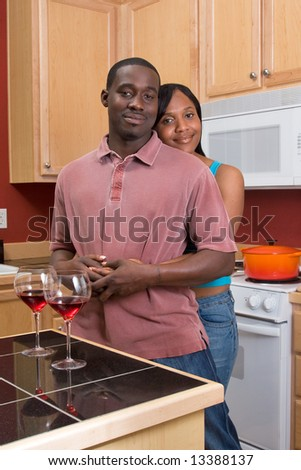 Attractive young african american couple standing in their kitchen with a neutral expression on their faces. She is standing behind him and hugging him. Vertically framed shot.