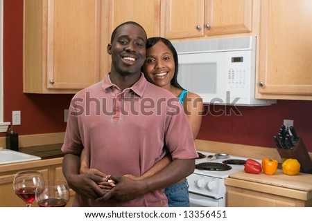 Attractive young african american couple standing in their kitchen with broad smiles on their faces. She is standing behind him and hugging him. Horizontally framed shot. - stock photo