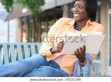 Attractive, young African-American female reading a book outdoors on a bench, street view, urban environment