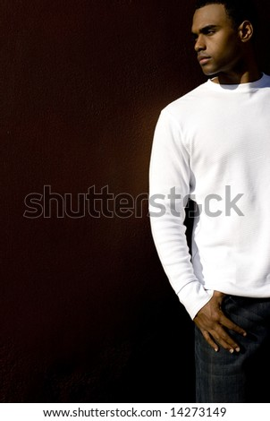 Attractive young African American male playing posing in a white t-shirt and jeans against a solid brown wall. - stock photo