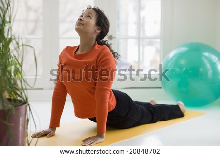 Attractive young African American woman in yoga Cobra pose - stock photo