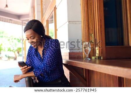 Attractive young african american woman sitting at bar smiling with mobile phone - stock photo