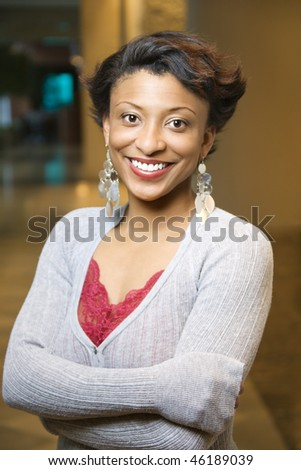 Attractive young African-American woman stands and smiles at the camera with crossed arms. Vertical shot. - stock photo