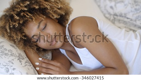 Attractive young african-american woman wakes up in her bedroom - stock photo