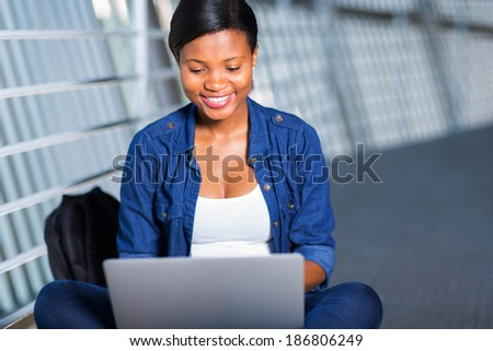 attractive young african college girl  using laptop computer - stock photo
