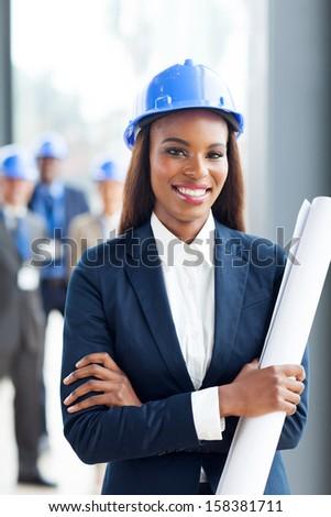 attractive young african construction manager holding blue print in office - stock photo
