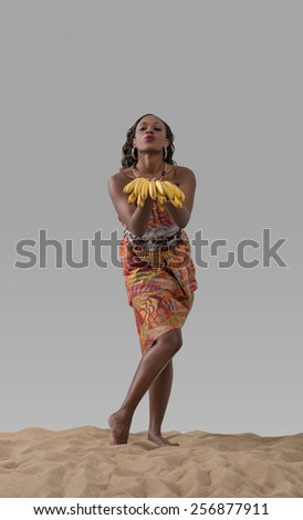 Attractive young african woman carrying bananas on sand on gray studio background - stock photo