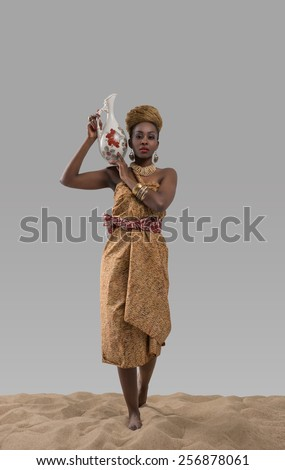 Attractive young african woman carrying jug with water on sand on gray studio background - stock photo