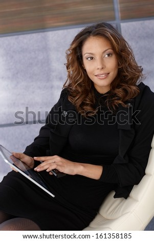 Attractive young afro businesswoman using tablet.